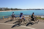 Group cycling along Manly Beach
